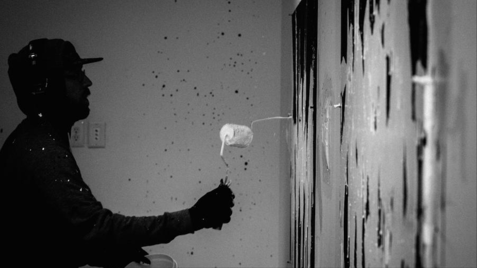A black and white image of a silhouetted man splattering paint on a wall.