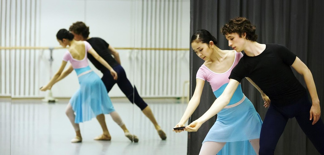 Members of the Junior Dutch National Ballet perform a dance while holding a phone together.