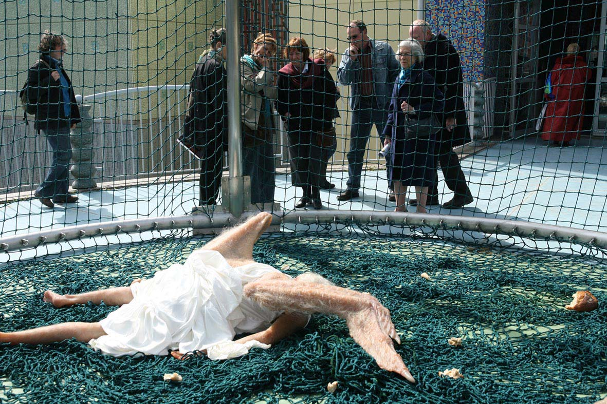 a sculpture of a fallen angel is stopping beijing in its tracks